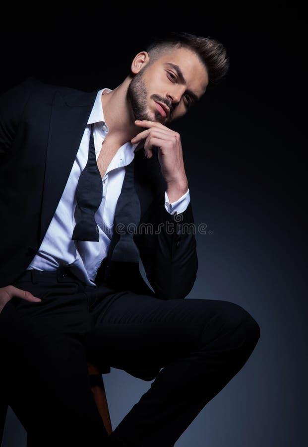 Homem elegante arrogante no smoking que guarda a mão no queixo foto de stock
