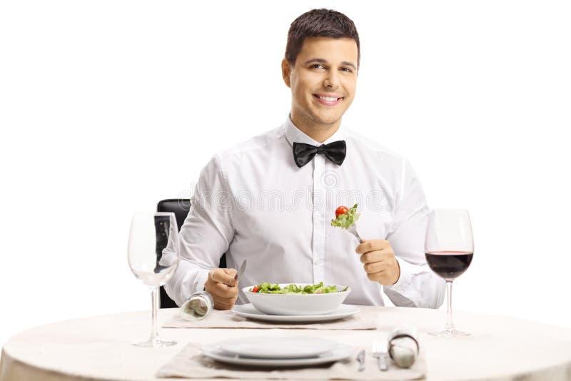 Homem elegante com um laço que come uma salada em uma tabela do restaurante imagens de stock royalty free
