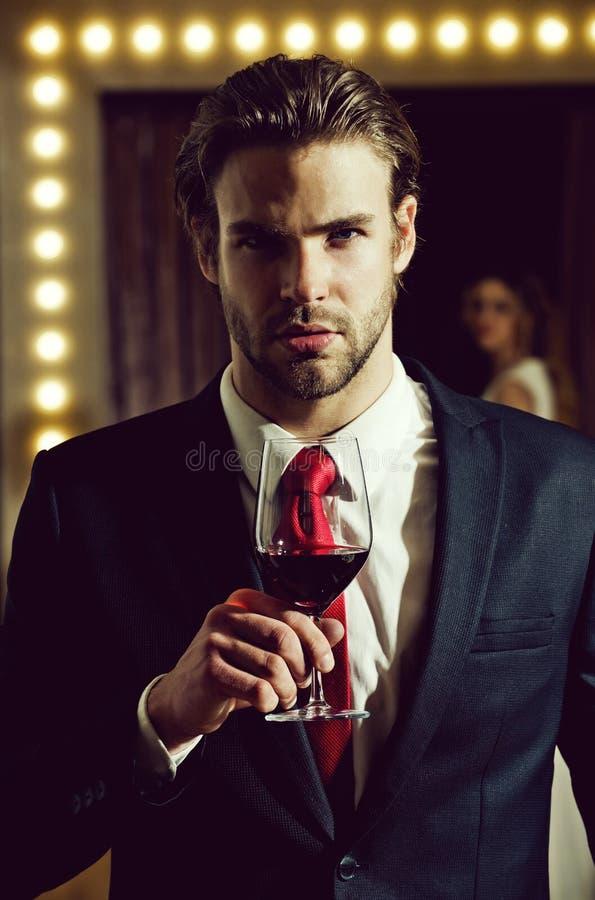 Homem elegante com um vidro do vinho tinto vidro de vinho da posse do homem, sommelier foto de stock royalty free