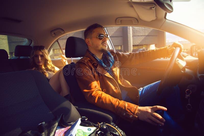 Homem elegante conduzido no assento traseiro uma menina impressionante imagens de stock royalty free