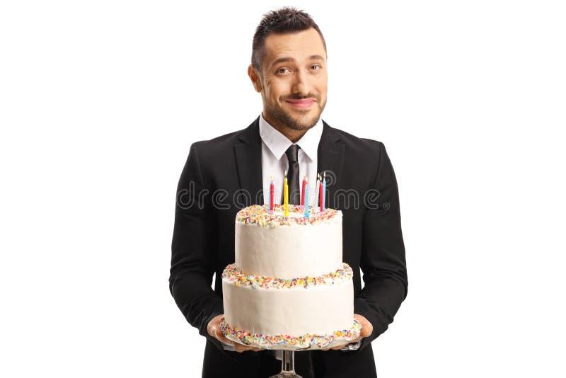 Homem elegante considerável em um terno que guarda um bolo com velas foto de stock