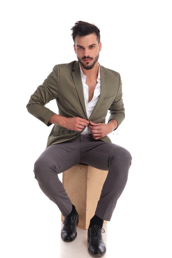 Homem elegante considerável que desabotoa o revestimento do terno ao sentar-se imagens de stock