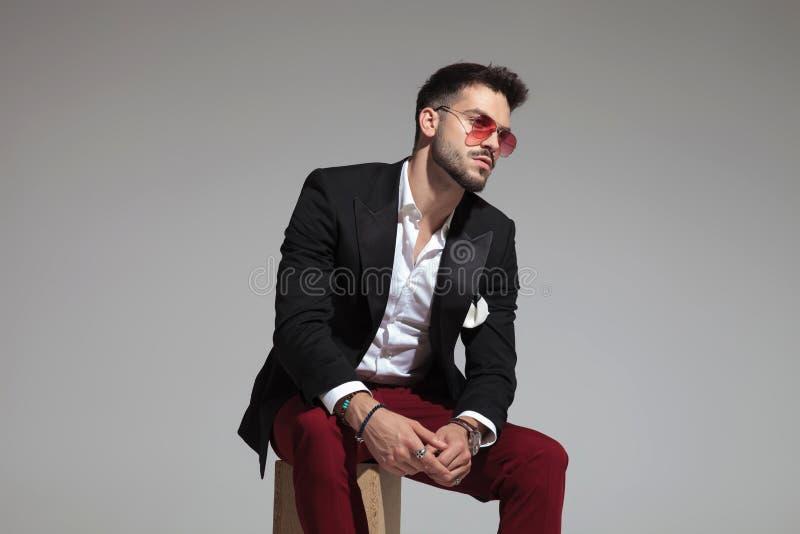 Homem elegante curioso que veste o terno e calças pretos de Borgonha foto de stock