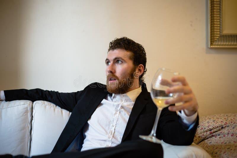 Homem elegante do moderno considerável que guarda o vidro do vinho imagens de stock royalty free