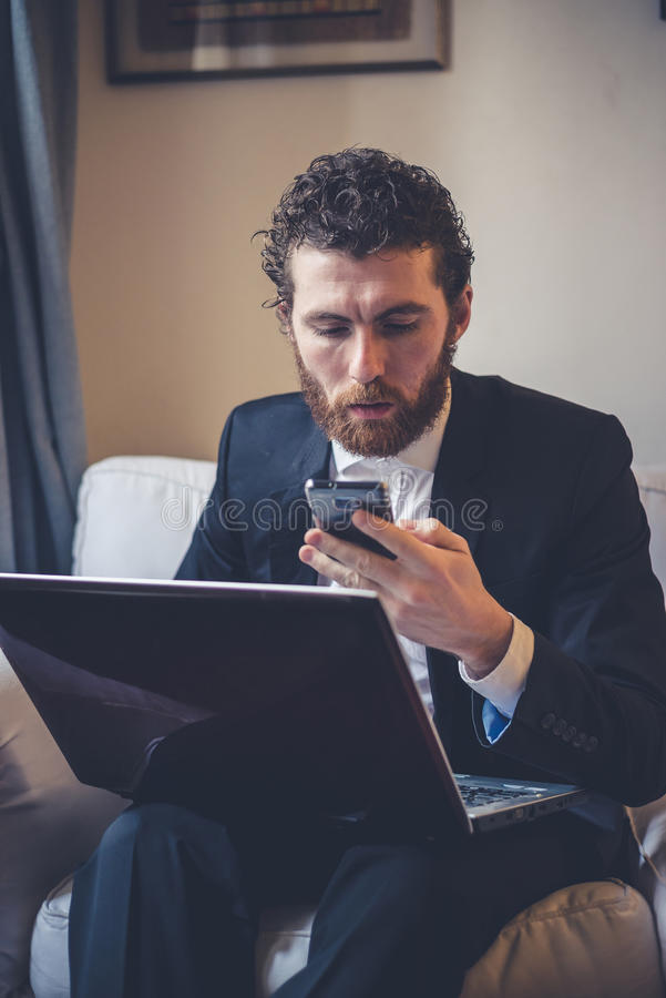 Homem elegante do moderno considerável que usa o portátil imagem de stock royalty free