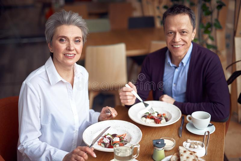 Homem elegante e mulher envelhecidos que têm o jantar no café imagens de stock