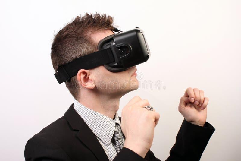 Homem elegante em um terno formal preto, vestindo uns auriculares da falha 3D de Oculus da realidade virtual de VR, pose de comba fotos de stock