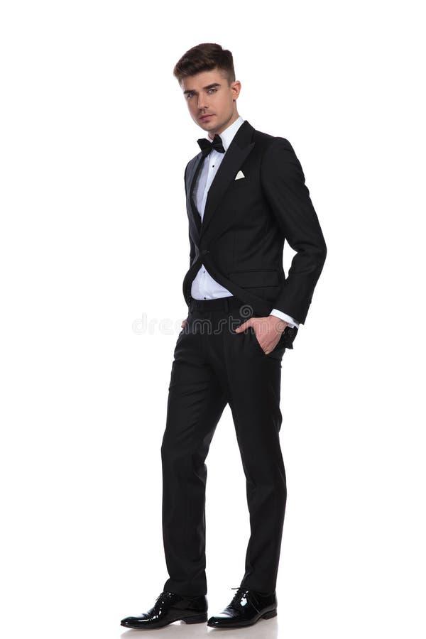 Homem elegante na posição preta do smoking com mãos em uns bolsos imagem de stock royalty free