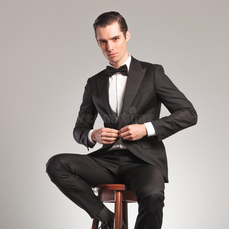 Homem elegante no smoking que abotoa seu revestimento ao sentar-se foto de stock