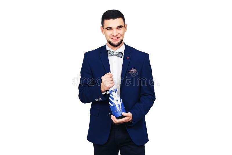 Homem elegante novo em um terno azul com uma garrafa decorada do champanhe ou do vinho foto de stock royalty free