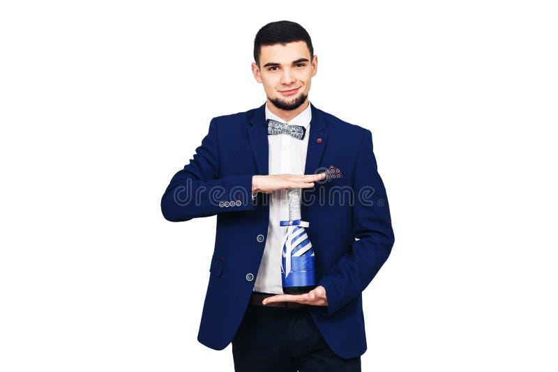 Homem elegante novo em um terno azul com uma garrafa decorada do champanhe ou do vinho foto de stock