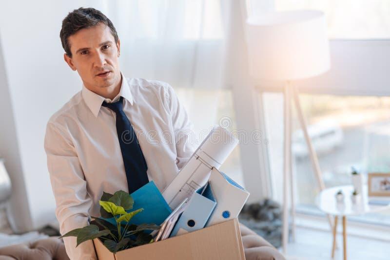 Homem elegante pensativo que leva uma caixa completamente de artigos pessoais fotografia de stock royalty free
