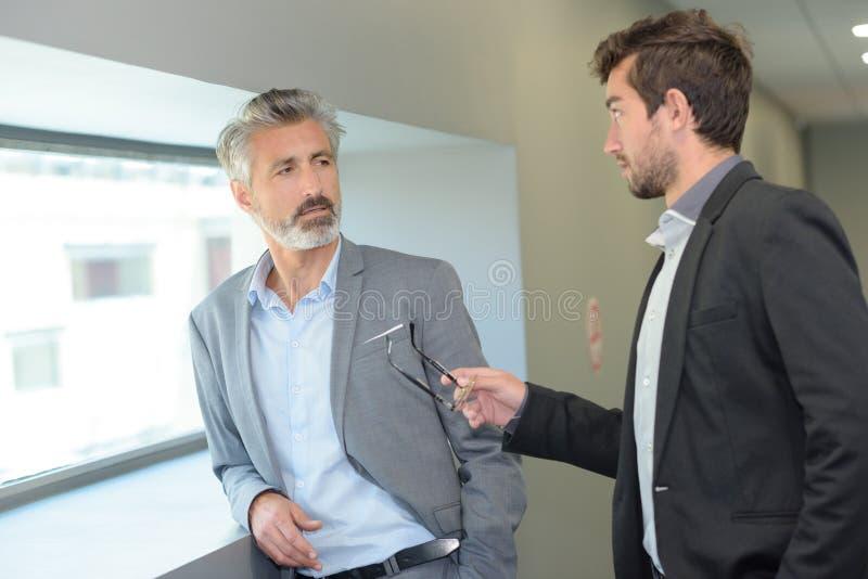 Homem elegante que fala ao workmate com gesticulação fotografia de stock royalty free