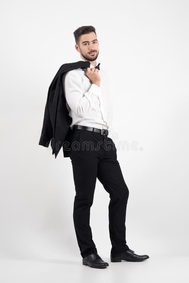 Homem elegante que guarda o revestimento do smoking sobre seu ombro que olha a câmera foto de stock royalty free