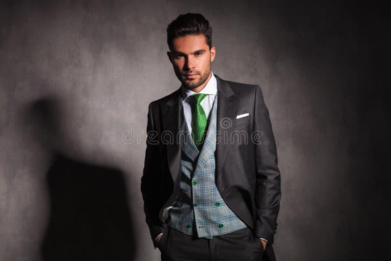 Homem elegante relaxado com mãos em uns bolsos que vestem o smoking fotos de stock
