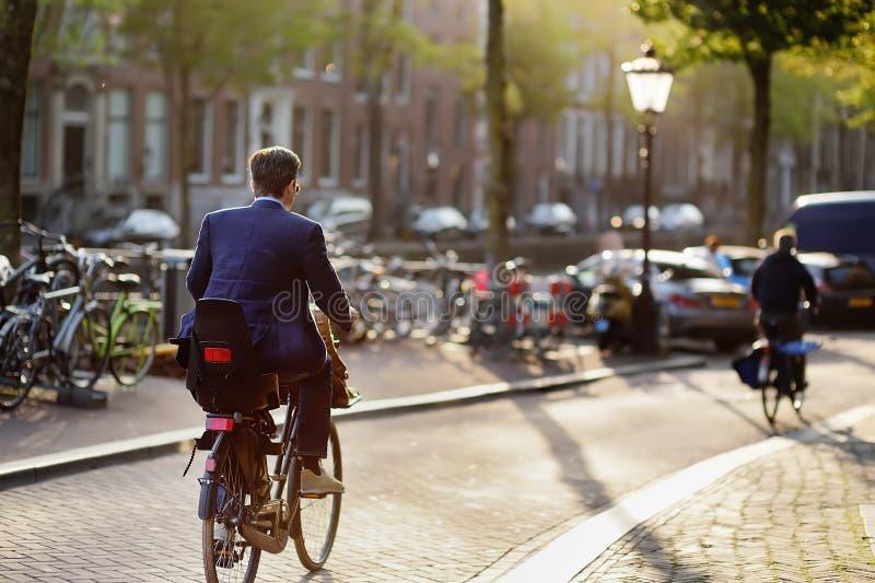 Homem elegantemente vestido que monta uma bicicleta na cidade histórica de Amsterdão imagens de stock royalty free