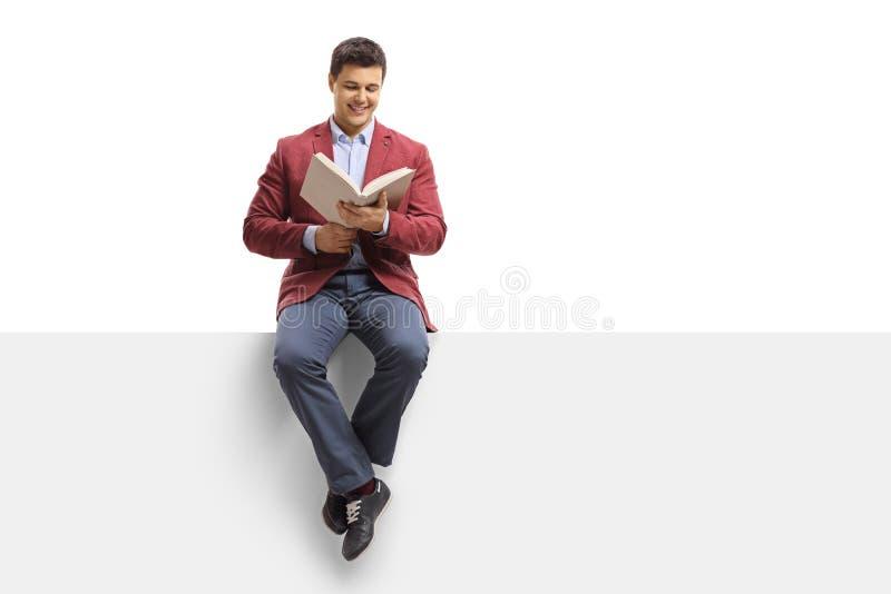 Homem elegantemente vestido que senta-se em um painel e que lê um livro fotos de stock