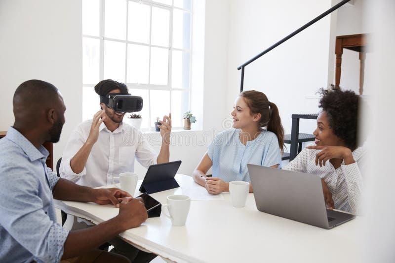 Homem em óculos de proteção de VR em uma mesa olhada por colegas no escritório foto de stock royalty free