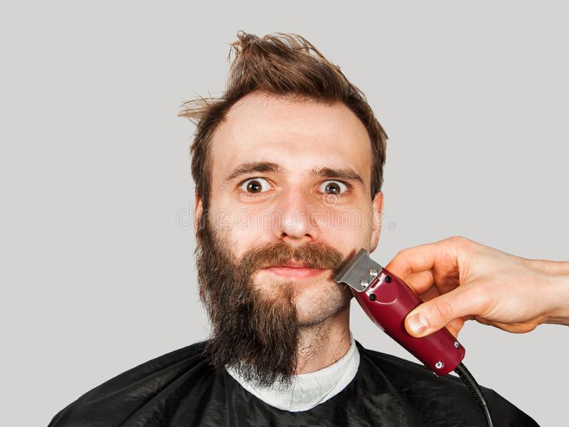 Homem em barbeações do barbeiro fora de sua barba com o ajustador no fundo cinzento fotos de stock royalty free