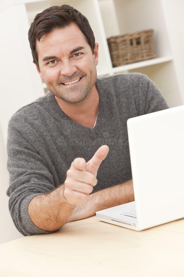 Homem em casa que usa o computador portátil e apontar imagem de stock royalty free