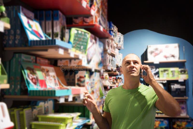 Homem em chamadas da loja à esposa imagens de stock royalty free