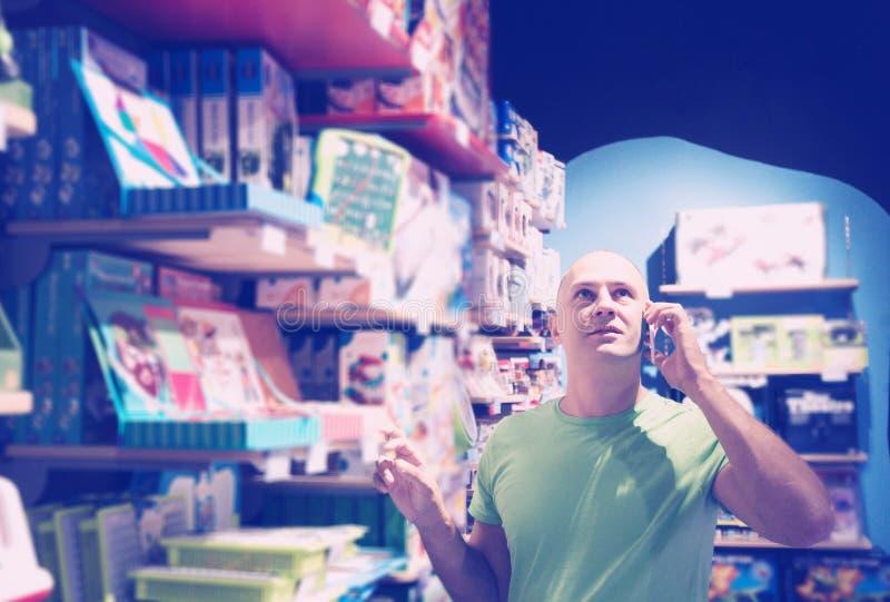 Homem em chamadas da loja à esposa fotografia de stock