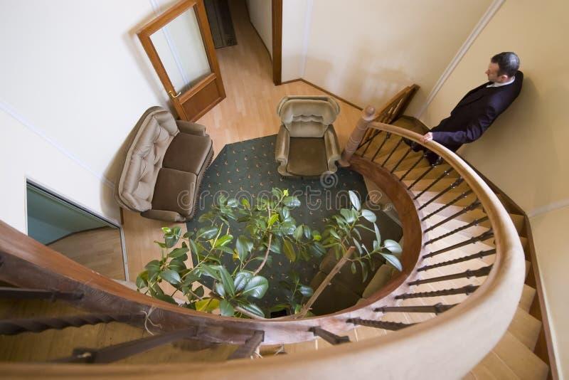 Homem em escadas espirais imagens de stock