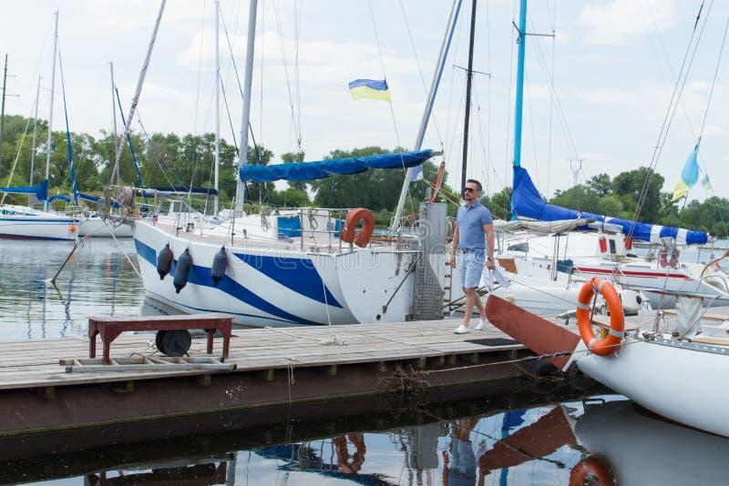Homem em férias que anda no porto do rio próximo dos barcos brancos com velas dobradas Viagem elegante nova do rio do começo do h foto de stock royalty free