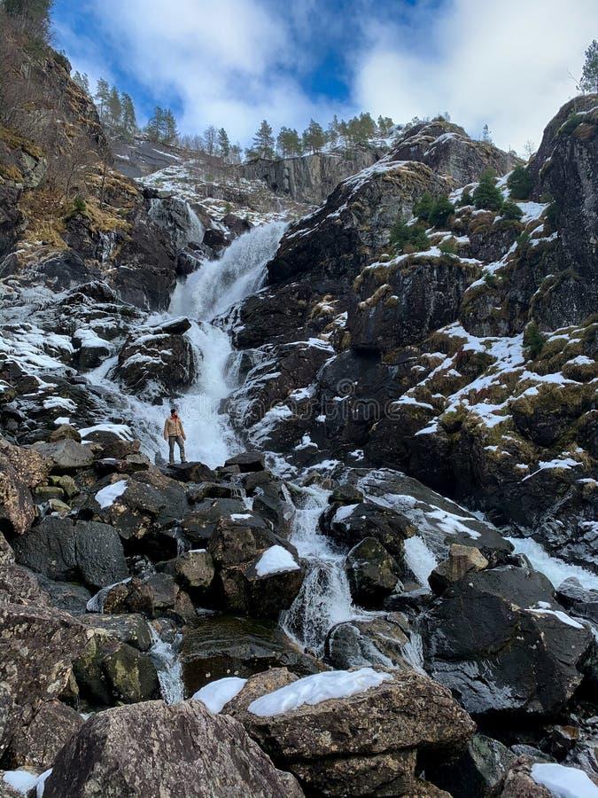 Homem em frente à queda de água de Latefossen no inverno, Noruega fotografia de stock royalty free