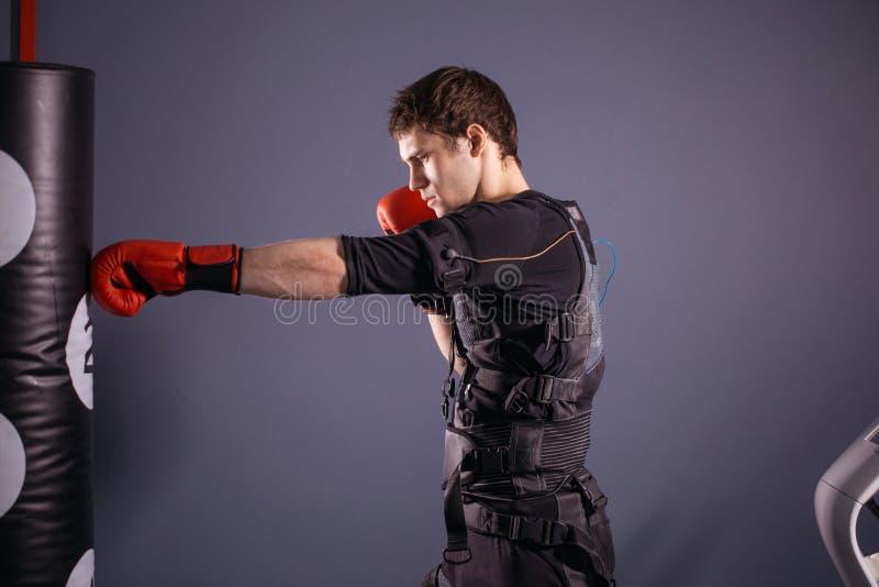 Homem em luvas de encaixotamento durante o treinamento pugilista no terno da estimulação elétrica imagens de stock