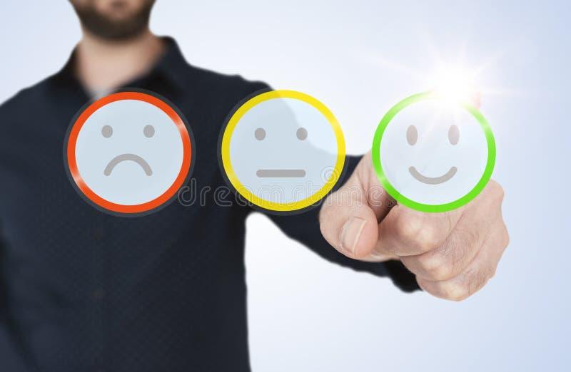 Homem em relação translúcida tocante com os botões do smiley da avaliação, conceito da camisa azul do feedback de cliente fotos de stock royalty free