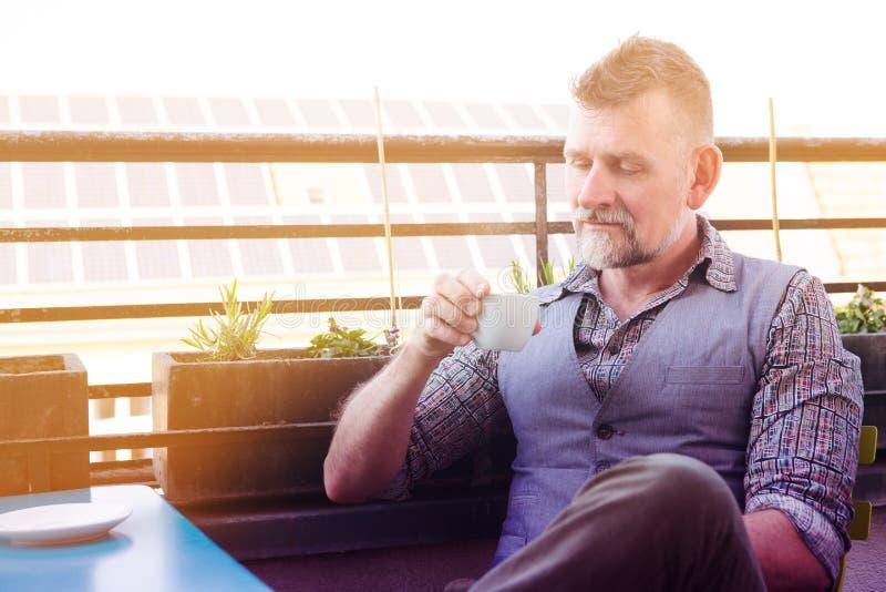 Homem em seu 50s que senta-se no balcão e no café bebendo foto de stock