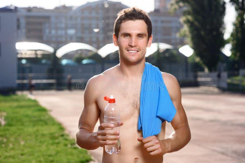 Homem em topless de sorriso com água foto de stock