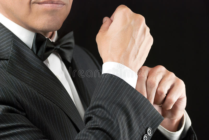 Homem em Tux Fixes Cufflink foto de stock royalty free