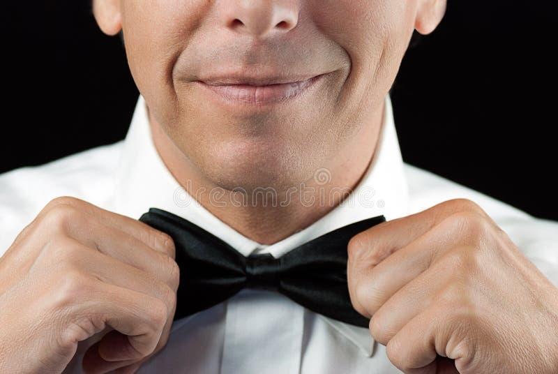 Homem em Tux Straightens Bowtie, duas mãos imagens de stock royalty free