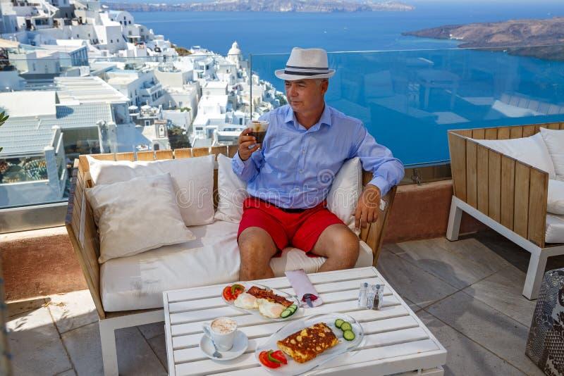 Homem em um café pelo mar fotos de stock royalty free