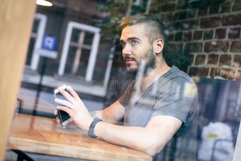 Homem em um café que olha pela janela imagens de stock