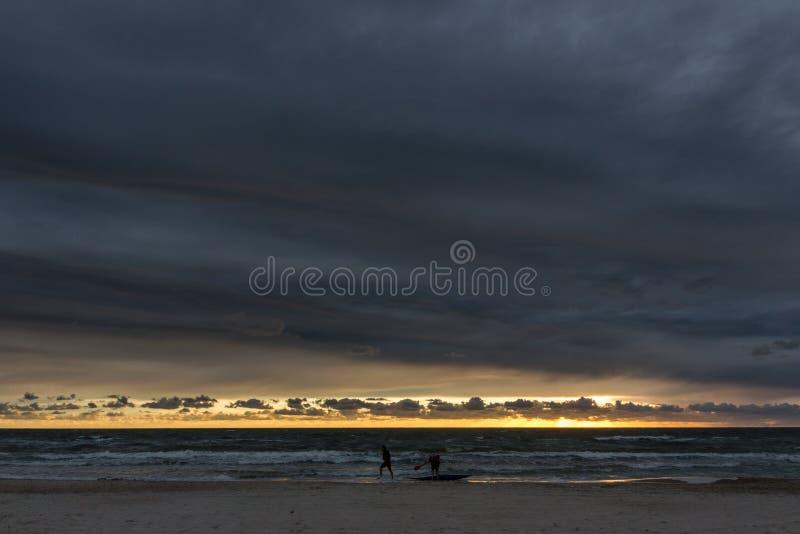 Homem em um caiaque no por do sol sobre o mar Báltico imagem de stock