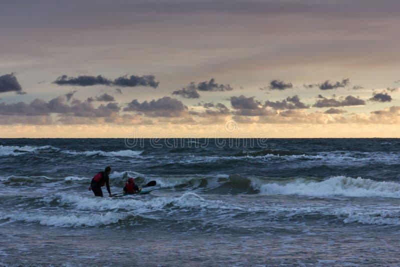 Homem em um caiaque no por do sol sobre o mar Báltico foto de stock royalty free