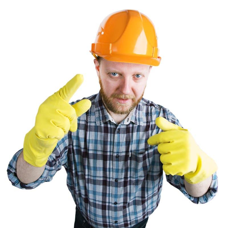 Homem em um capacete e em umas luvas amarelas imagens de stock royalty free