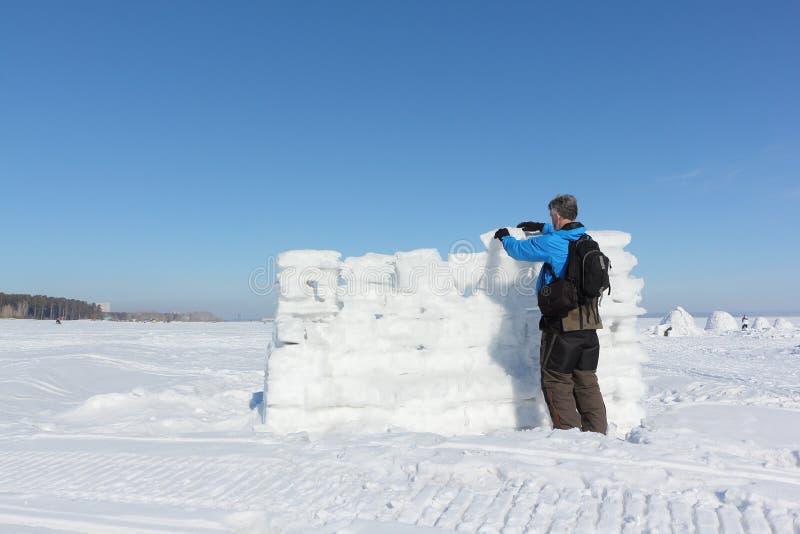 Homem em um casaco azul que constrói uma parede da neve imagem de stock