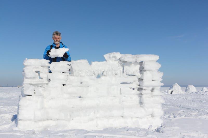 Homem em um casaco azul que constrói uma parede da neve fotografia de stock royalty free