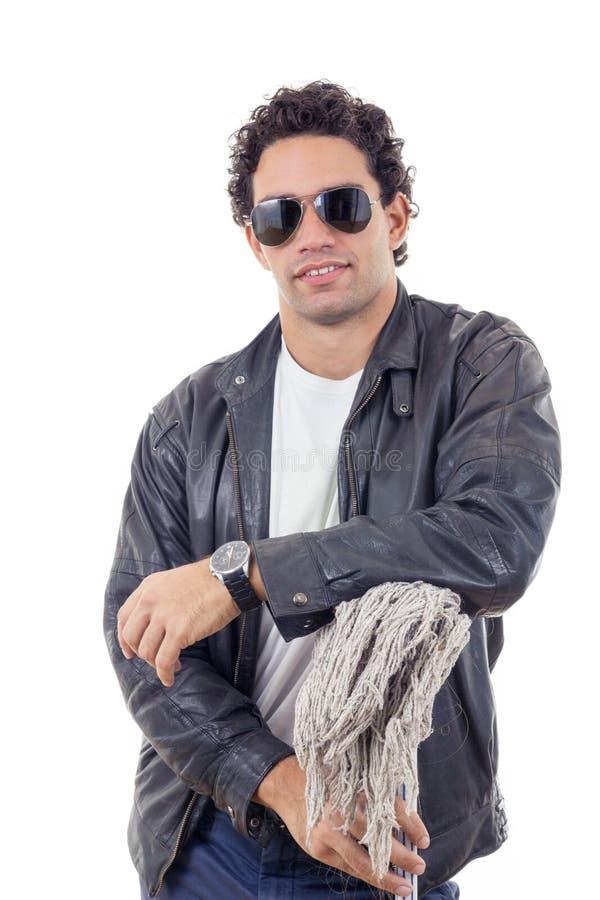 Homem em um casaco de cabedal que inclina-se em uma vassoura foto de stock