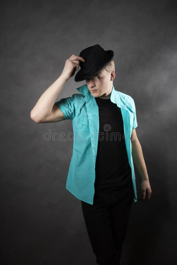 Homem em um chapéu com um fundo cinzento fotografia de stock