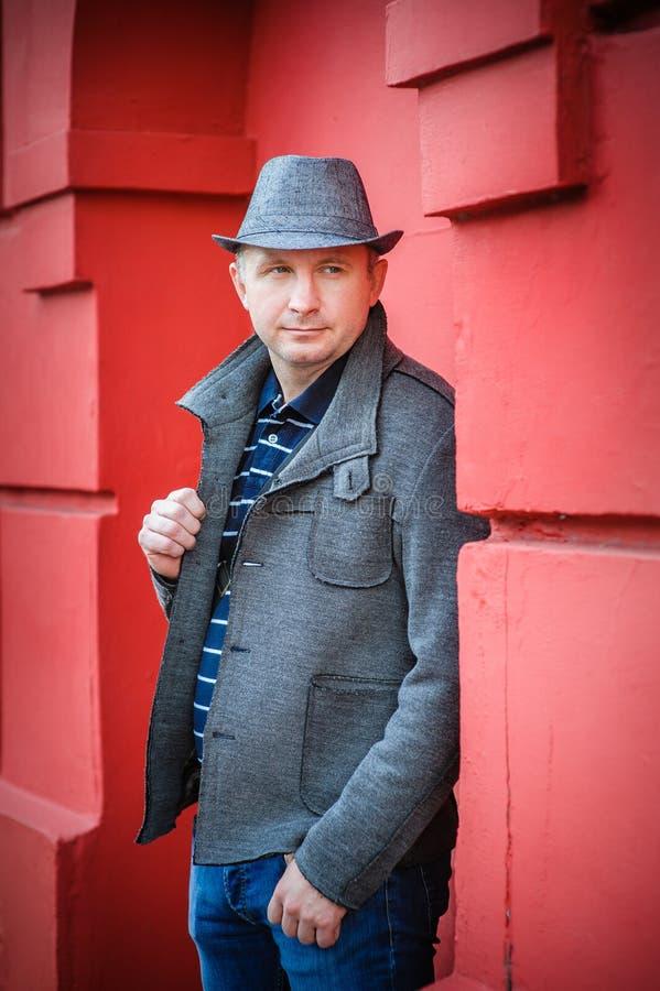 Homem em um chapéu perto da parede vermelha foto de stock