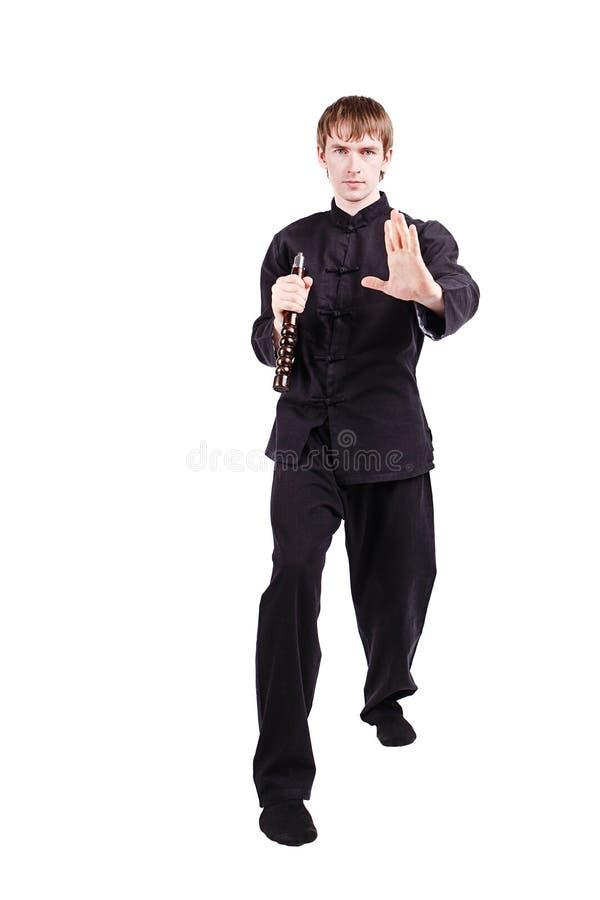 Homem em um kung-fu praticando do quimono com nunchaku foto de stock