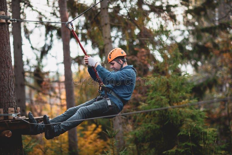 Homem em um parque em um parque da aventura Cidade da corda parque do país para esportes imagem de stock royalty free