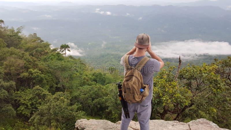 Homem em um penhasco que fotografa o vale e a selva imagens de stock