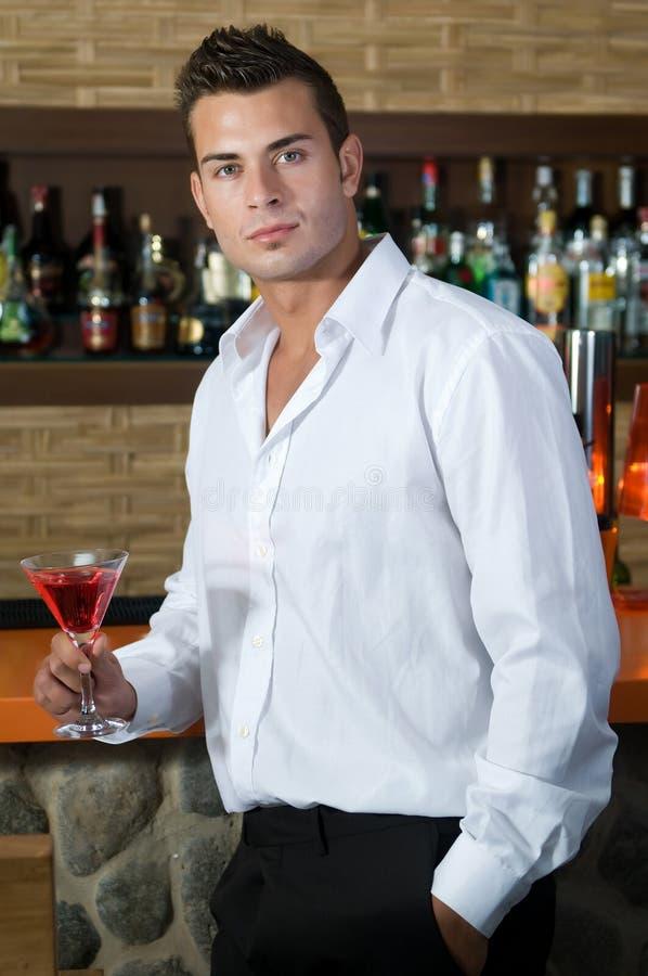 Homem em um pub com martini vermelho fotos de stock royalty free