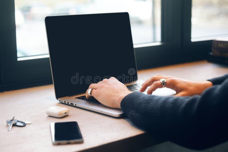 Homem em um restaurante Freelancer com um portátil O homem de negócios e começa acima Portátil com o spase vazio da cópia do espa imagens de stock